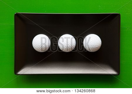 Black ceramic dishes with golf balls on over green background rectangle dish