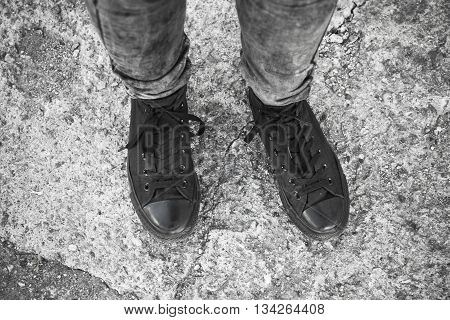 Feet In Black Gumshoes And Gray Jeans