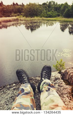 Feet In Camouflage Pants And Black Shoes
