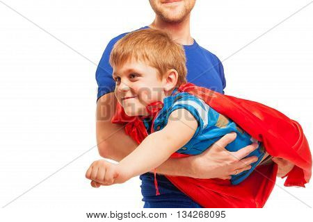 Kid boy playing superman wearing red cape, as his dad helping him to fly, isolated on white