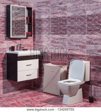 Inside of fashionable bathroom - toilet and sink and modern ceramic tiles in red color