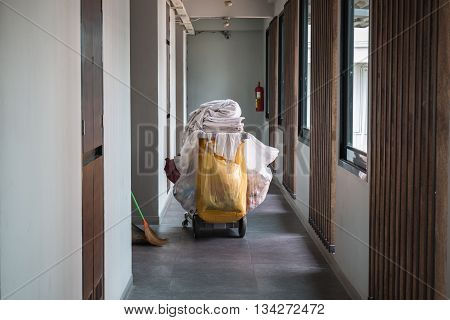 Maid's cart with a towel in hotel corridor