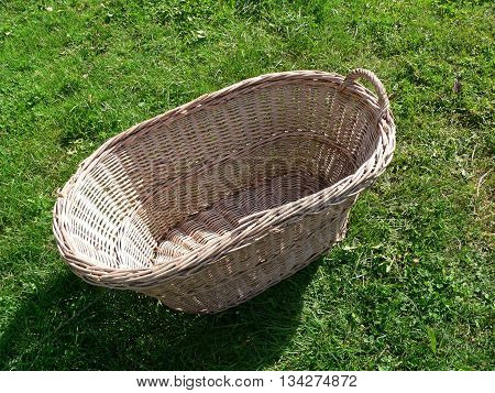empty wicker laundry basket lying in the grass