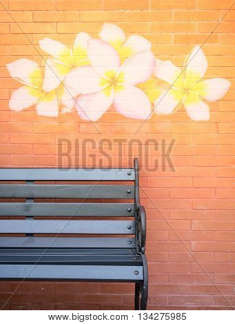 Black bench in front of flower painting alike processed brick wall