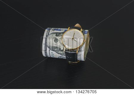 gold watch dressed in hundred dollar bills, time is money