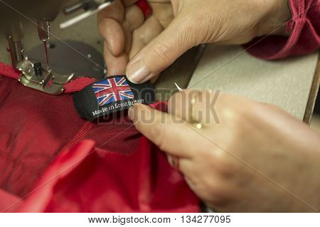 "A ""Made in Britain"" clothing tag about to be sewn on to red piece of cloth poster"