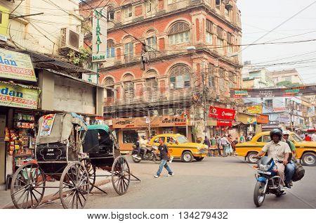 KOLKATA, INDIA - JAN 16, 2016: Motorcycle driving on busy street with car traffic and antique rickshaw cart on January 16, 2016 in Calcutta. Kolkata has a density of 814.80 vehicles per km road length