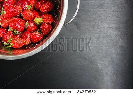 strawberries in a colander on a black desktop background