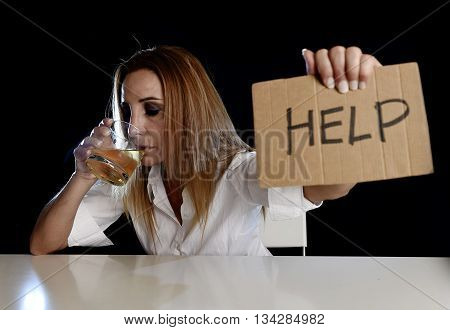 drunk alcoholic blond woman drinking whiskey glass asking for help holding message board depressed wasted and sad isolated on black background in alcohol abuse and housewife alcoholism