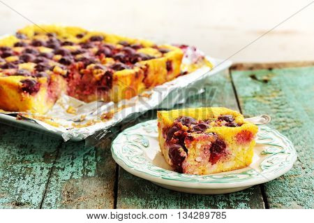 Homemade quark pie with cherries and red peony falling petals on old wooden background closeup