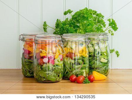 Prepared salad in four glass storage jars on a kitchen worktop.
