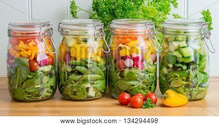 Prepared salad in glass storage jars. Four in a line on a wooden kitchen worktop.