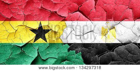 Ghana flag with egypt flag on a grunge cracked wall
