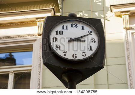 Old clock with white dial and black hands a symbol of the passage of time.