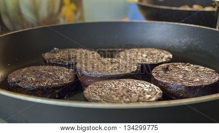 Breakfast of traditional sliced black pudding frying in a pan
