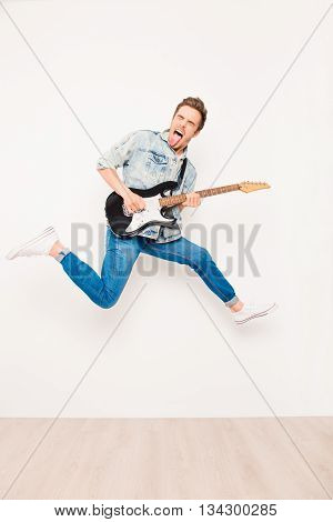 Young Rocker Playing On Electro Guitar, Showing Tongue  And Jump
