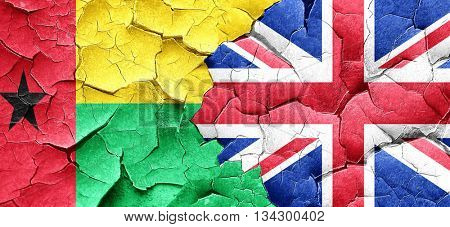 Guinea bissau flag with Great Britain flag on a grunge cracked w