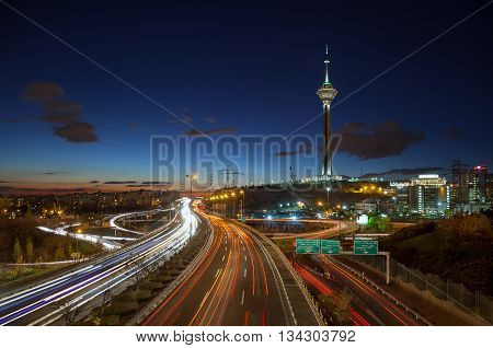TEHRAN IRAN - DECEMBER 4 2015: Illuminated Milad Tower behind highways of Tehran filled with passing cars. Milad Tower is the second most important landmark of Tehran after Azadi Monument.