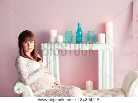 Beautiful pregnant woman 20-24 year old sitting in room over white fireplace with decorations. Looking at camera. Maternity. Motherhood.