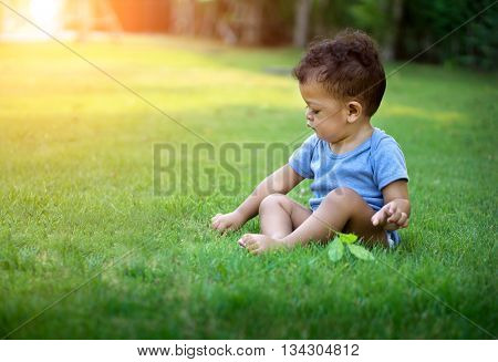 Asian Baby Boy Sitting In Green Nature