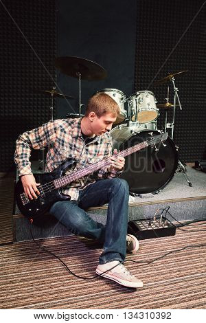 Bass guitar player sitting near drum set at music studio. Musician performing composition on bass guitar. Front view on playing bass guitar player at sound recording studio