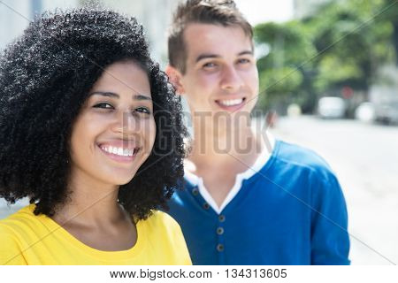Laughing latin woman with curly black hair and boyfriend in the city in the summer