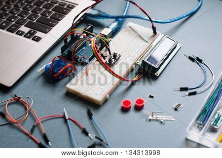 Engineer background with microcontroller and different details on black table. Engineer workplace, prepared for upgrading laptop. Microcontroller with necessary for programming work details
