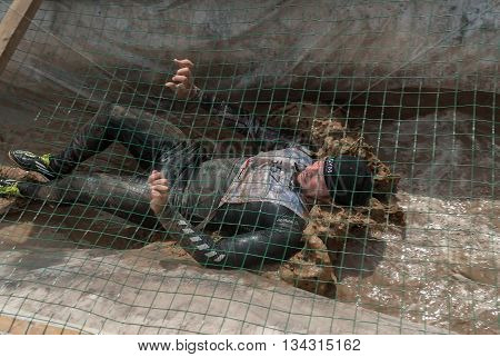 Tyumen Russia - June 11 2016: Race of Heroes project on the ground of the highest military and engineering school. Guardroom stage. Man creeps on an entrenchment with sand and water under net