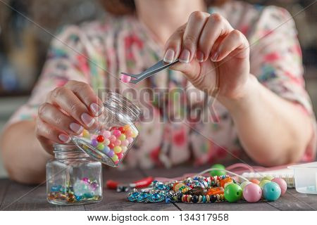 Home enthusiasm jewelry. Woman making home craft art