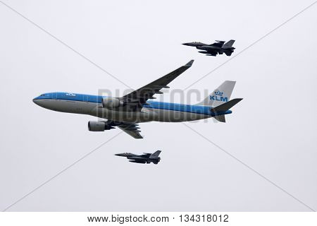 LEEUWARDEN, NETHERLANDS - JUNI 11 2016: Dutch KLM Boeing escorted by two F16 aircraft of the Dutch air force