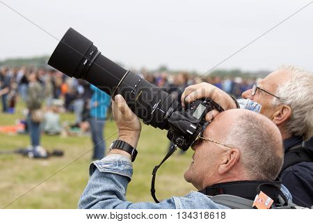 Leeuwarden , the netherlands - 11 juni 2016:  Photographer with a Nikon camera and Sigma 80-400mm lens photo, s of planes at an air show