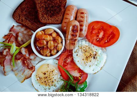 Traditional Full English Breakfast - Sunny-side-up Fried Eggs, Sausages, Beans, Toast And Bacon