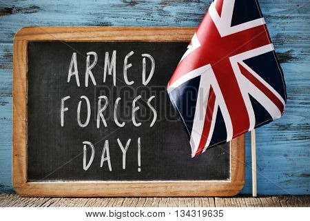 the text armed forces day written in a chalkboard and a flag of the United Kingdom, on a rustic wooden background