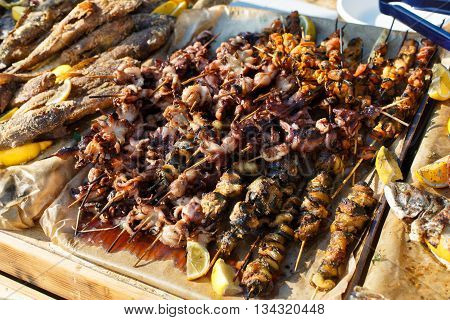 Plenty of seafood, fish, octopus, mussels grilled at barbecue. Seafood bbq outdoors at picnic, party. Street food, seafood takeaway at big tray. Grill at bamboo sticks.