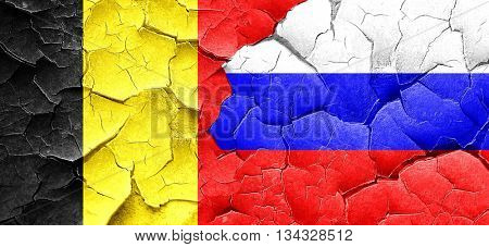 Belgium flag with Russia flag on a grunge cracked wall