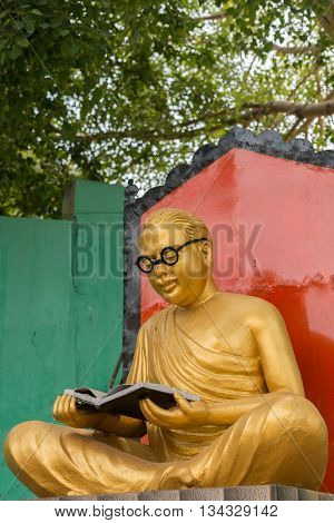 Chettinad India - October 17 2013: Golden statue of the actor and politician C.N Annadurai in the Karaikudi City. He reads a book and has black rimmed glasses. Green background.