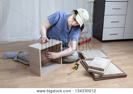 Self  assembling furniture at home the woman tightens the screw that secures the handle drawers.