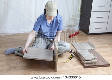 Furniture Assembly Portrait Of Woman Carpenter Assembling Furniture At Home.