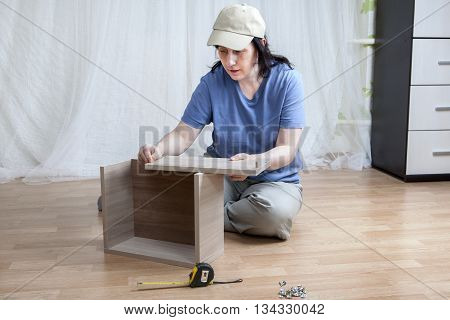 One Caucasian woman self assembly new furniture sitting on the floor.