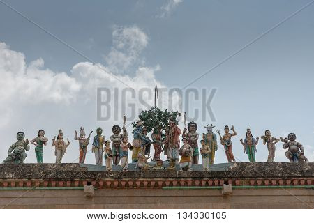 Chettinad India - October 17 2013: Row of statues shows the wedding of Shiva with Meenakshi and plenty of guests such as Vishnu Ayyanar and Hayagriva. Against blue sky.