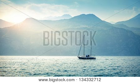 Landscape panorama with sailer boat ship sailing by lake or sea waves in evening sunset sun sunbeams high mountains at background garda veneto region italy