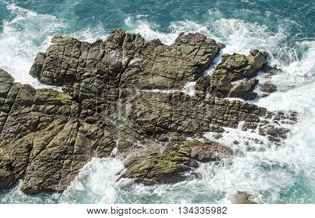 Eroded rock surrounded by foaming waters in the Pacific Ocean