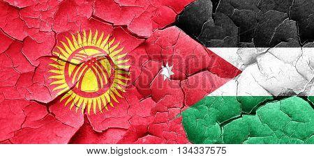 Kyrgyzstan flag with Jordan flag on a grunge cracked wall