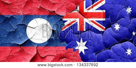 Laos flag with Australia flag on a grunge cracked wall