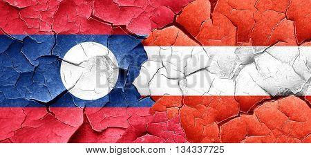 Laos flag with Austria flag on a grunge cracked wall