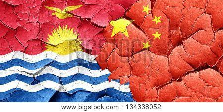 Kiribati flag with China flag on a grunge cracked wall