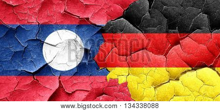 Laos flag with Germany flag on a grunge cracked wall