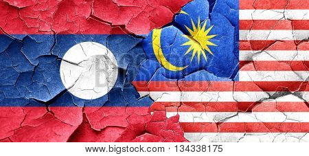 Laos flag with Malaysia flag on a grunge cracked wall