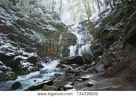 Waterfall in mountains at wintertime
