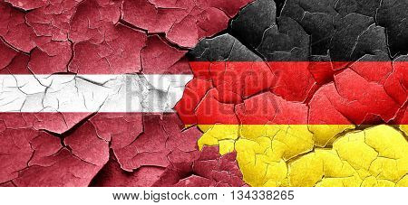 Latvia flag with Germany flag on a grunge cracked wall